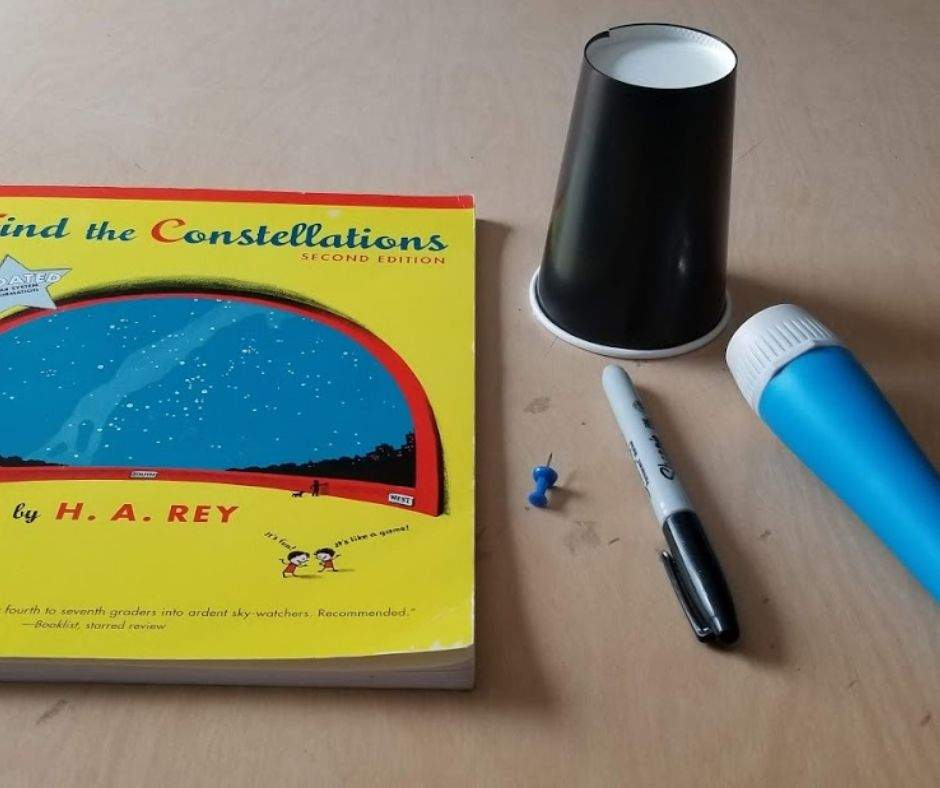 H.A. Rey's Find the Constellations, a paper cup, a marker, a push pin, and a flashlight