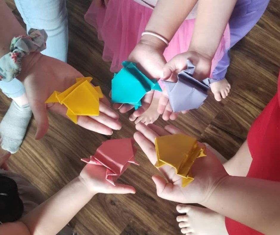 five hands holding origami frogs in a circle
