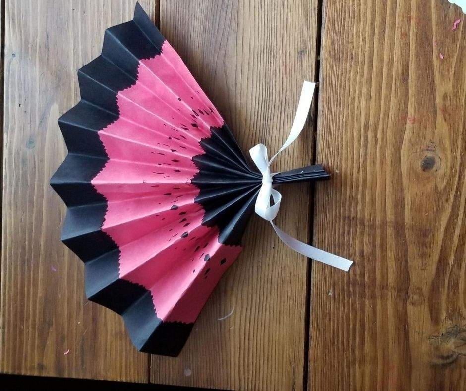 finished paper fan with ribbon tied on the handle